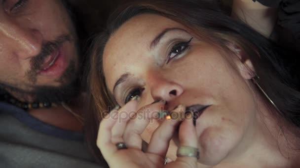 Young Woman Smoking Marijuana Cigarette With Boyfriend At Home