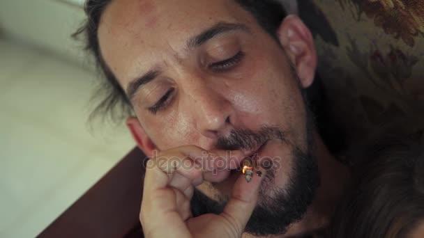 Junger Mann und Frau rauchen zu Hause Marihuana-Zigarette