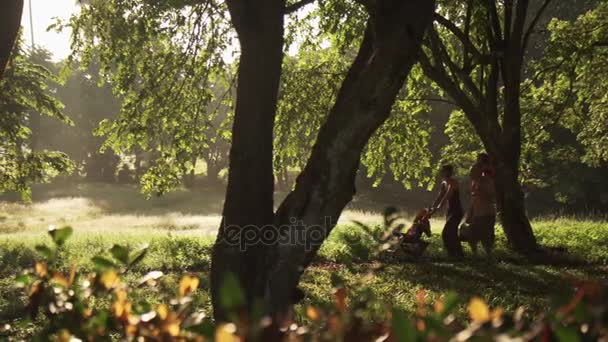 Happy White Family Walking In City Park With Picnic Basket