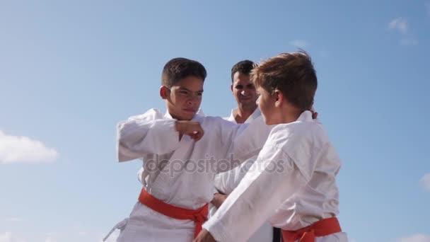 Děti bojovat s učitelem ve škole Karate zpomaleně