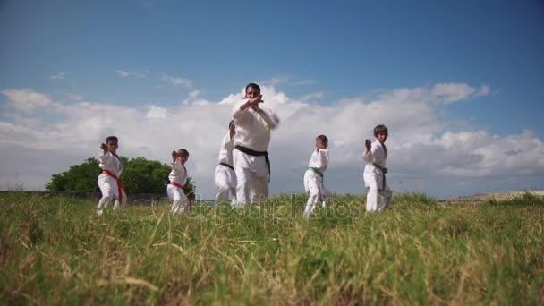 Škola karate s trenéry a chlapci se zpomaleně