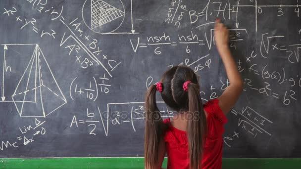 Šťastná dívka psaní na tabuli ve třídě a usmívá se