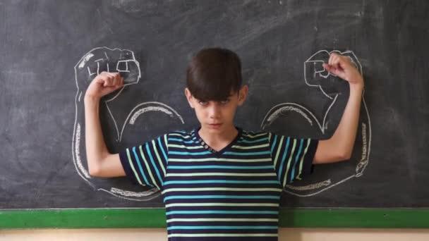 Silného mužského potomka ukazuje svaly v učebně na lekci
