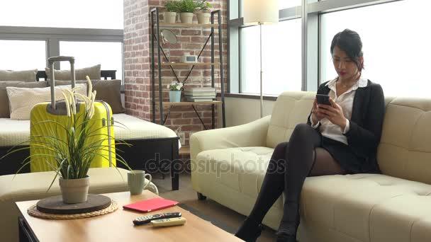 Obchodní cesty asijské ženy obchodnice s Smartphone v hotelovém pokoji