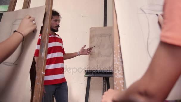 Muž v práci jako učitel na umělecké škole se studenty