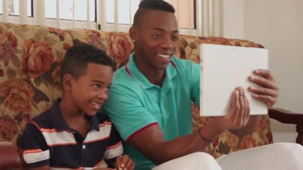 Otec a syn hrát hru s přenosným počítačem na pohovce