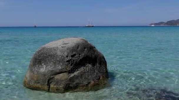 lone rock facing the mediterranean sea on italian sandy beach