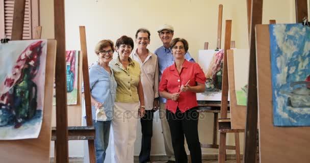 Skupina starších lidí se usmívá na kameru na umělecké škole