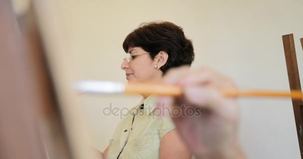 Starší žena se usmívá na kameru během lekce umění