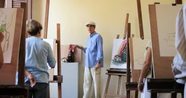 Učitel při práci ve třídě malířství s starší studenti