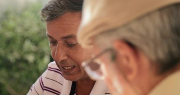 Uomo anziano felice 32 sorridente e giocare a Domino con gli amici