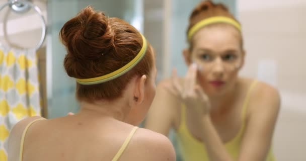 Young Woman Applies Beauty Cream On Face Smiling