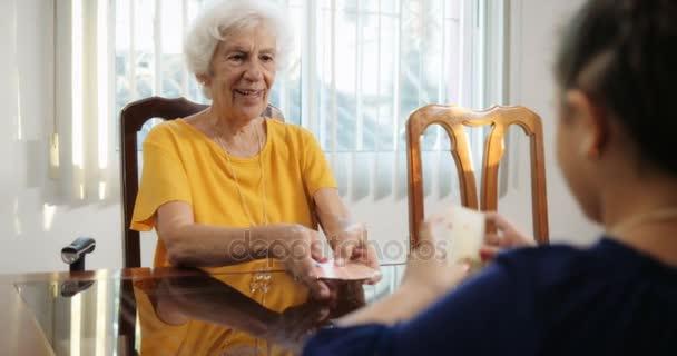 Vnouče a babička doma hraje kouzelnické triky s kartami