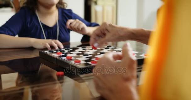 Nonna che gioca Checkers gioco con la nipote da tavolo a casa