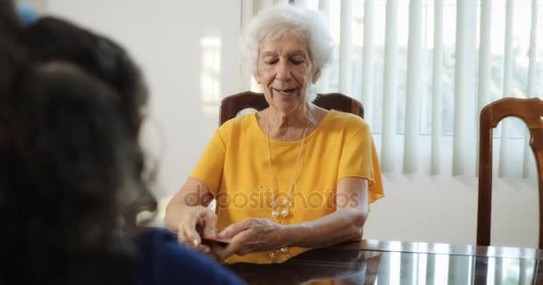Granddaughter And Grandma Playing Magic Tricks With Cards At Home