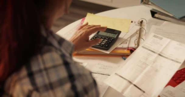 Starší žena doma pomocí kalkulačky pro daně a rozpočet