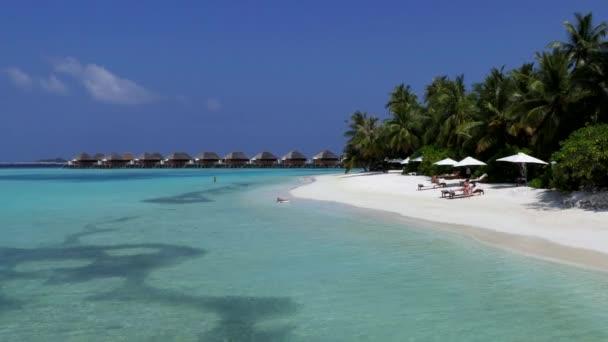 Maledivy - února 2018 - bílý písek pláží v Vakarufalhi atoll, Maledivy, Asie, Indický oceán. Lidé, plavání a relaxaci během svátků v exkluzivní resort. Modré moře vody, korálové útesy a palm stromy. Cestování a cestovní ruch