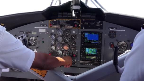 Blick auf das Cockpit eines am Himmel fliegenden Kleinflugzeugs. Team von Piloten im Flugzeug, Besatzung berühren Ausrüstung und Befehle auf dem Armaturenbrett. Luftfahrt, Reisen, Arbeit, Beruf