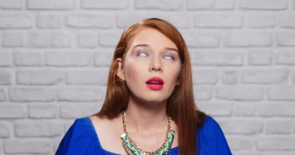 Výrazy obličeje mladé Zrzky ženy na cihlové zdi