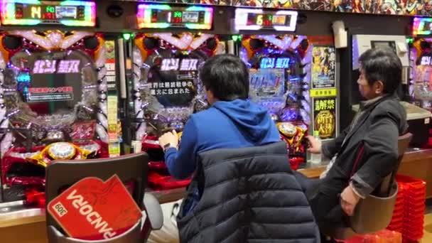 Tokio, Japonsko - březen 2018 - japonští muži hrající pachinko, loterie, arkáda, videohry, video hry, hazardní hry, hrací automaty v asijské kasino. Tokyo, Japonsko, Asie