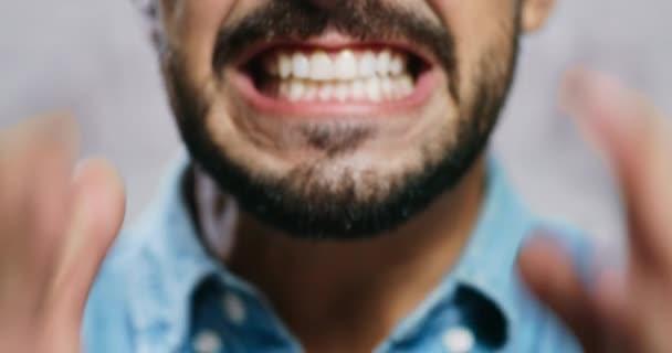 Gesichtsausdruck junger Mann mit Bart auf Ziegelmauer