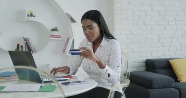 Černá žena platí on-line nákup kreditní kartou po nakupování. Afričtí Američané používají kartu pro internetovou transakci. Dívka s notebookem PC doma