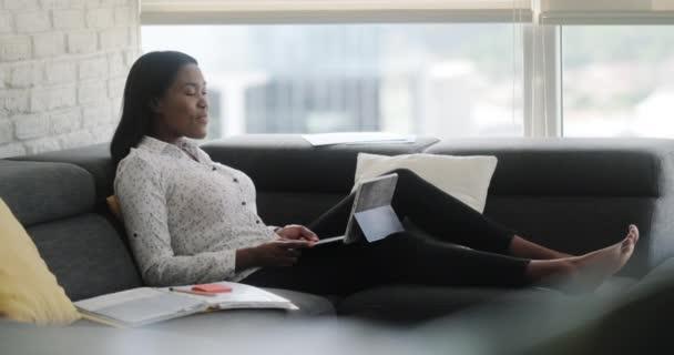 Porträt einer schwarzen Frau, die von zu Hause aus Meetings oder Webkonferenzen abhält. Afroamerikaner bei Fernarbeit. Junge Geschäftsfrau arbeitet mit Laptop, liegt auf Sofa