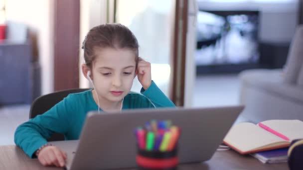 Holčička studuje s notebookem. Smutná studentka učící se s počítačem. Nudné dítě, které dělá domácí úkoly a e-learning během pandemie koronaviru. Vzdálené vzdělávání doma