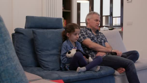 Movie at home with divorced dad and daughter. Unhappy family with man and female child watching television and sitting on sofa at home, snorting while watching boring show or film on TV