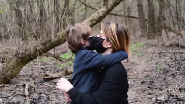 Woman and son in forest in black medical mask from Covid-19 virus