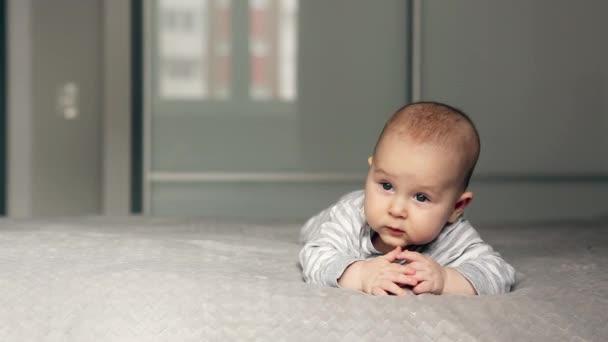 Nádherné děťátko leží na posteli a dívá se do kamery
