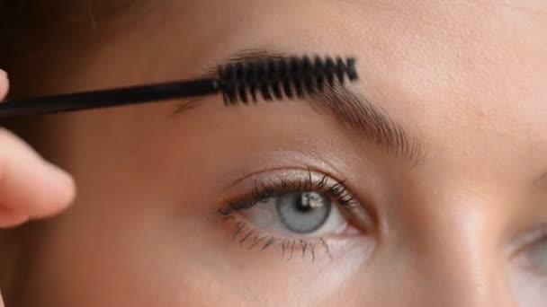 Eye in macro footage of young woman applying makeup on her eyebrows