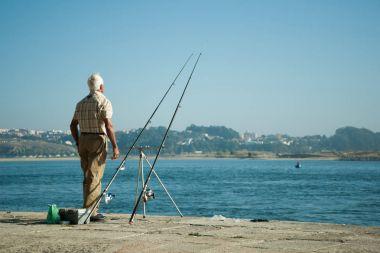 Senior man fishing on the coast of the ocean