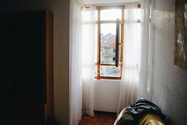 Open wooden window with white curtains