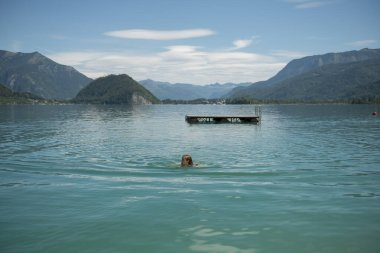 Young woman swimming in lake during sunny day