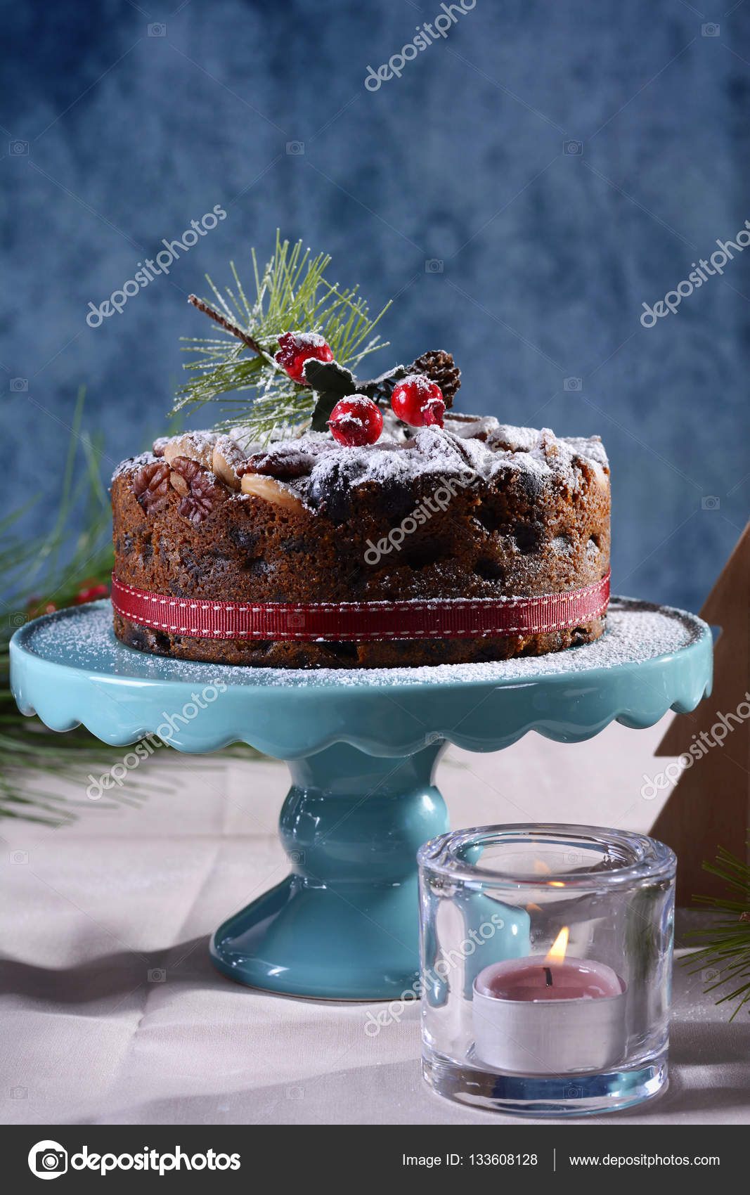 Festive holiday table with English style Christmas fruit cake with glamorous table setting with pink candles and blue background. \u2014 Photo by amarosy & Festive holiday table with English style Christmas fruit cake ...