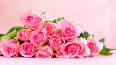 Pink roses on pink wood table, Mothers Day background with copy space.