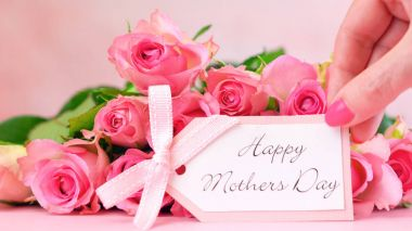 Pink roses on pink wood table, Mothers Day background closeup.