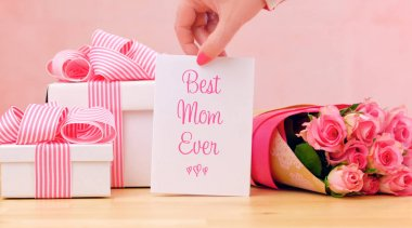 Mothers Day gift, pink roses and Best Mom Ever greeting card on table.