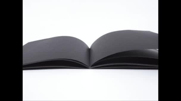 Stop motion animation, Nyissa meg a fekete notebook olvasni a fehér háttér.