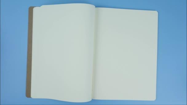 Otevřete bílou stránku knihy Prázdný pro vložení textu a titulků na modré pozadí.