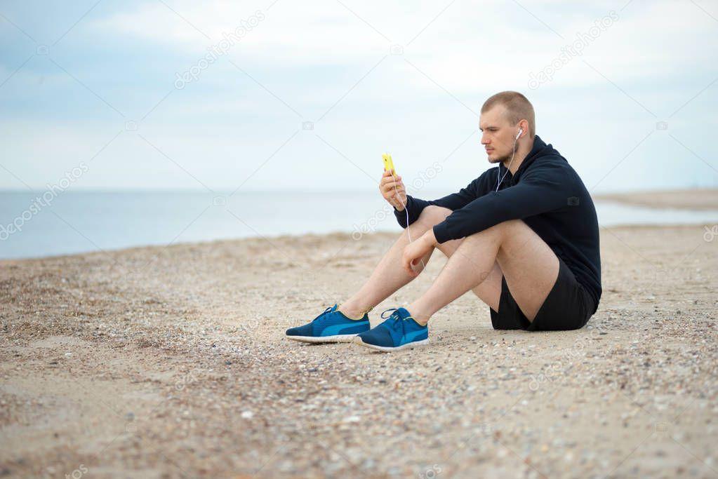 man on the beach listening to music