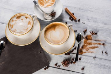 A cup of cappuccino on the white wooden background