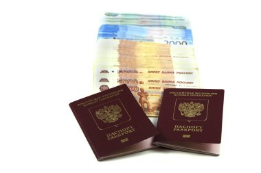 Two Russian passports with a bunch of rubles in denominations of five, two and one thousand rubles. The concept of immigration, tourism, travel to the resort. Buying a passport or a deposit, a large sum of money is a million rubles. Isolated on a whi