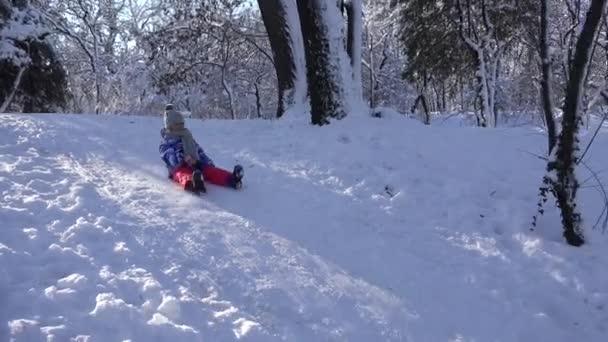 Kinderrodeln im Schnee, Kind spielt im Winter, kleines Mädchen im Park