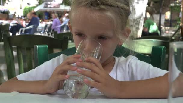 4K Kid Trinkwasser, gelangweilte kleine Mädchen Kinderporträt Gesicht spielen mit Wasserglas im Restaurant