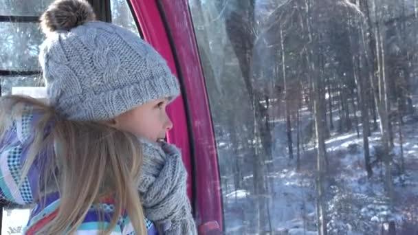 Gyerek sífelvonó télen, gyermek kábelkocsiban, lány a hegyekben, kilátás az Alpokban, alpesi