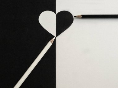Valentine's Day. Concept. Heart, pencils on white, black background. Yin Yang. View from above. Copy space