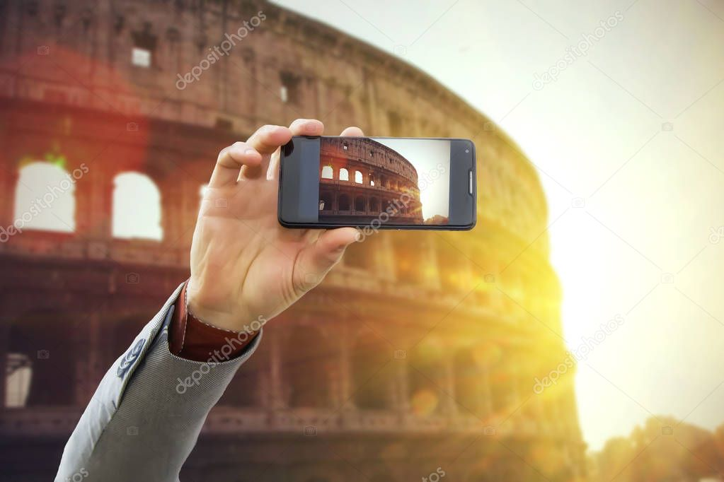 Фотообои Tourist taking a picture in front of Colosseum at spring sunset, Rome, Italy. Travel concept