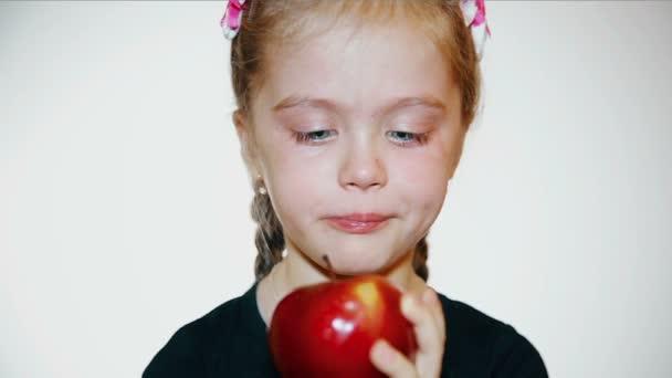 sad little girl eats a red apple